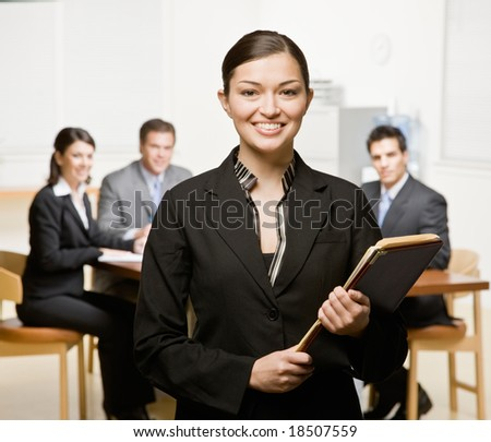 Confident businesswoman with notebook and co-workers in conference room - stock photo
