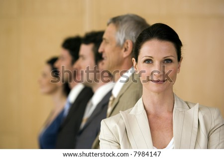 Confident businesswoman with team behind