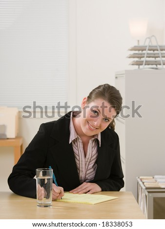 Confident businesswoman writing on legal pad taking notes - stock photo