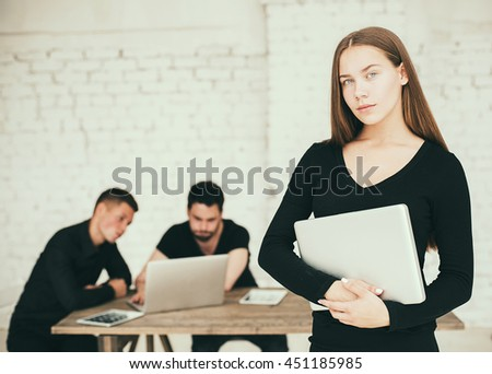 Confident businesswoman. Young woman holding notepad and looking at camera while his colleagues discussing something in the background - stock photo