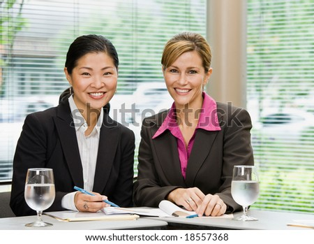 Confident businesswomen posing in conference room - stock photo