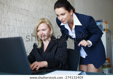 Confident businesswomen team communicate by laptop in office - stock photo