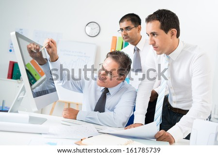 Confident busnessman pointing at computer screen while explaining idea to his colleagues at meeting - stock photo