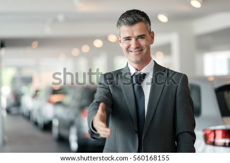 Confident car dealer giving a handshake, car showroom on the background