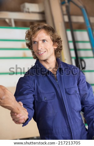Confident carpenter shaking hands with colleague in workshop - stock photo