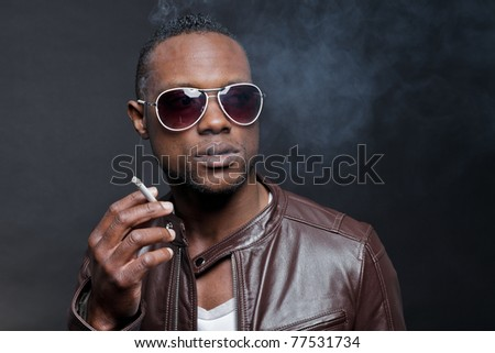 Confident casual young black man wearing brown leather jacket and sunglasses smoking cigarette. Studio portrait against dark background.