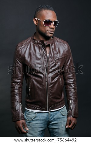 Confident casual young black man wearing brown leather jacket and sunglasses. Studio portrait against dark background. - stock photo