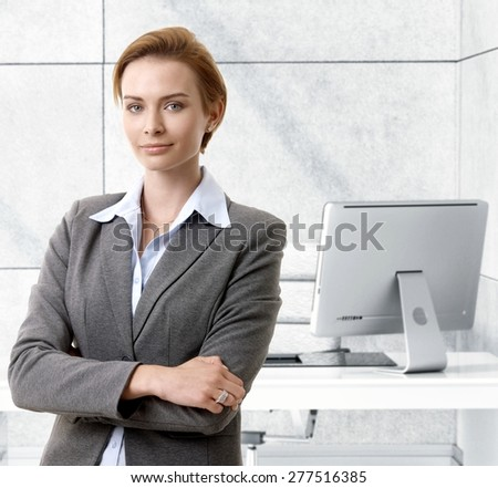 Confident caucasian businesswoman standing at office desk, smiling. - stock photo