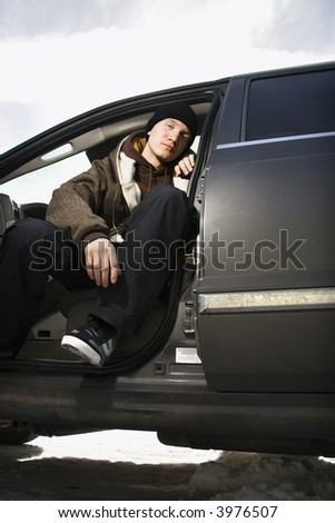 Confident Caucasian male teenager sitting in car.