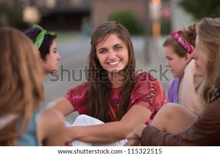 Confident Caucasian teenage girl with group of friends - stock photo