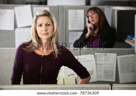 Confident Caucasian woman employee standing in her cubicle - stock photo