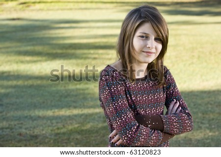 Confident child, 11 years, looking at camera with arms crossed