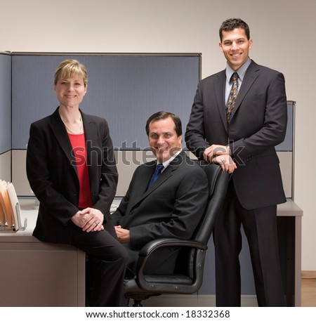Confident co-workers posing in cubicle - stock photo
