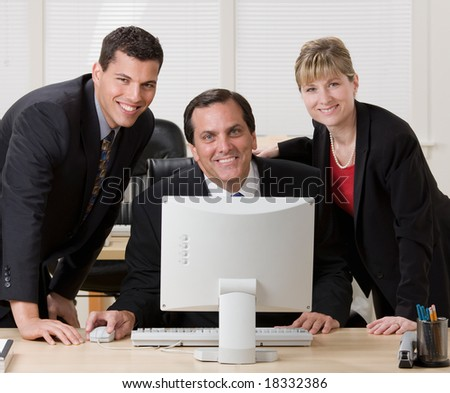 Confident co-workers posing together at desk