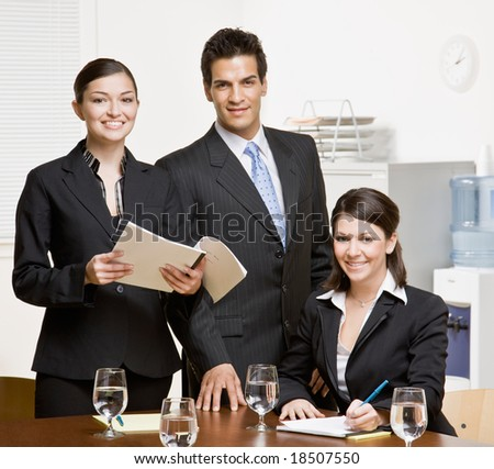 Confident co-workers with paperwork in conference room - stock photo