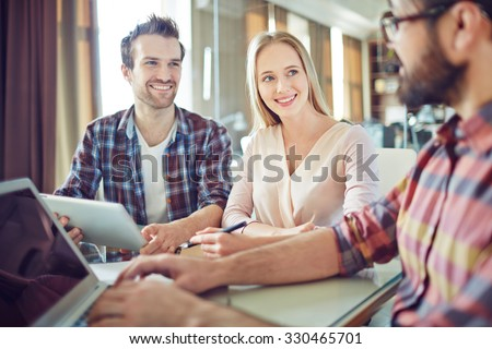 Confident colleagues looking at their co-worker during consultation - stock photo