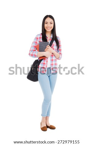 Confident college student. Full length of young Asian teenage girl in holding textbook and smiling while standing against white background - stock photo