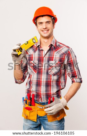 Confident contractor. Handsome young handyman with tool belt carrying work tool on shoulder and smiling while standing against grey background - stock photo