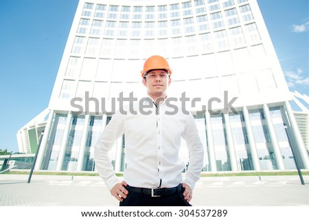 Confident contractor. Serious young man in shirt and hardhat smiling while standing outdoors - stock photo