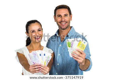 Confident couple holding money on white screen
