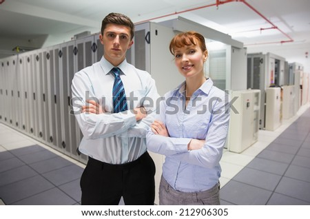 Confident data technicians looking at camera in large data center - stock photo