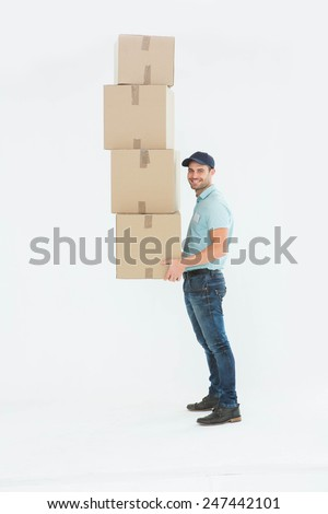 Confident delivery man carrying stack of boxes on white background - stock photo