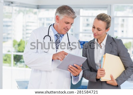 Confident doctor and pretty businesswoman discussing in medical office - stock photo