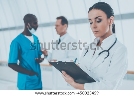 Confident doctor. Beautiful female doctor writing something at her clipboard while her colleagues talking in the background - stock photo
