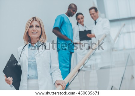 Confident doctor. Confident female doctor moving downstairs and smiling while her colleagues talking in the background - stock photo