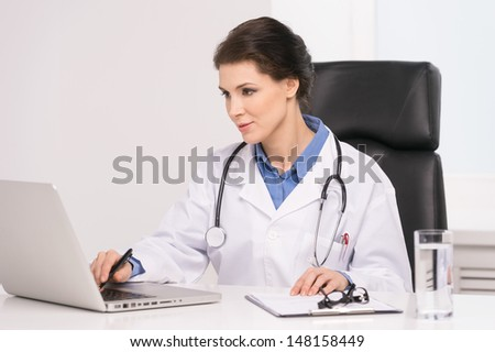 Confident doctor. Confident middle-aged female doctor sitting at her working place and working at the computer - stock photo