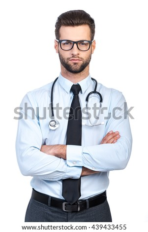 Confident doctor. Confident young handsome man in shirt and tie carrying stethoscope on shoulders and looking at camera while standing against white background  - stock photo