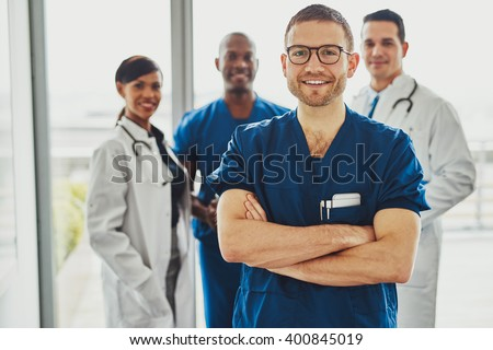 Confident doctor in front of group smiling at the camera, wearing surgeon clothes - stock photo