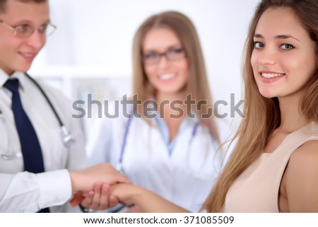 Confident doctor looking at  patient while speaking to her, woman doctor in the background. Medical and health care concept