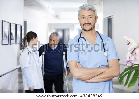 Confident Doctor Standing With Colleague And Senior Patient In B - stock photo