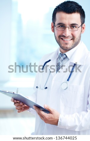Confident doctor with stethoscope and clipboard looking at camera - stock photo