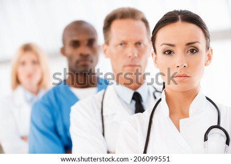 Confident doctors team. Confident female doctor looking at camera while her colleagues standing in a row behind her - stock photo