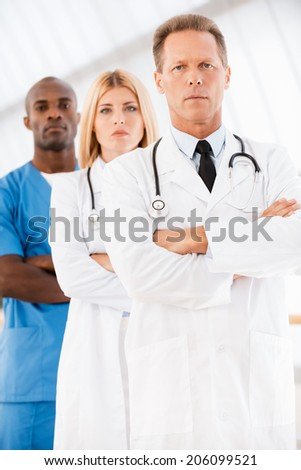 Confident doctors team. Confident male doctor looking at camera and keeping arms crossed while his colleagues standing in a row behind him - stock photo
