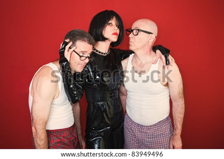 Confident dominatrix holds two insecure men around her. - stock photo