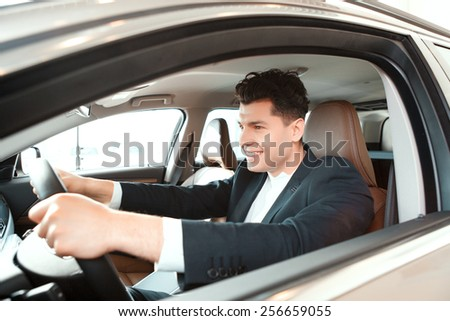 Confident drive. Portrait of a smiling handsome man in suit sitting on drivers place in car and touching the steering wheel in car dealership - stock photo
