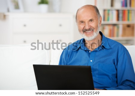 Confident elderly man giving the camera a beautiful smile using a laptop while relaxing on a couch at home in his living room - stock photo