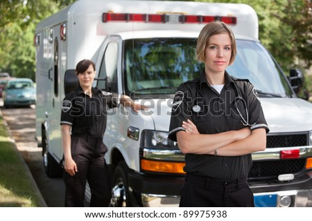 Confident emergency medical team portrait standing with ambulance in background