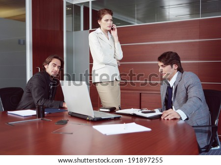 confident employees looking at monitor while their boss talking by phone  - stock photo