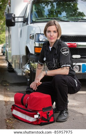 Confident EMS paramedic kneeling by portable oxygen unit and ambulance - stock photo