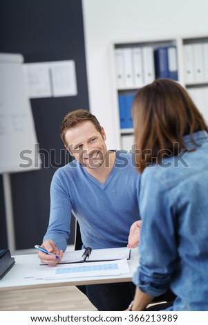 Confident enthusiastic business team having a discussion at a table in the office with focus to a handsome young man doing paperwork and gesturing with his hand - stock photo