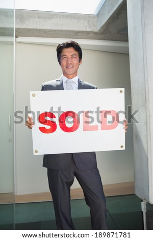 Confident estate agent standing at front door showing sold sign outside a house