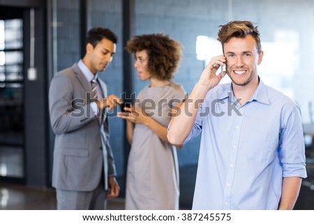 Confident executive talking on mobile phone with his coworkers in the background - stock photo