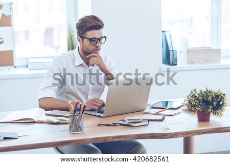 Confident expert at work. Pensive young handsome man using his laptop while sitting at his working place - stock photo