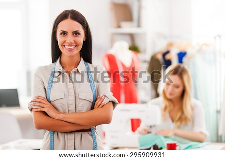Confident fashion expert. Cheerful young woman keeping arms crossed and smiling while another woman sewing in the background  - stock photo