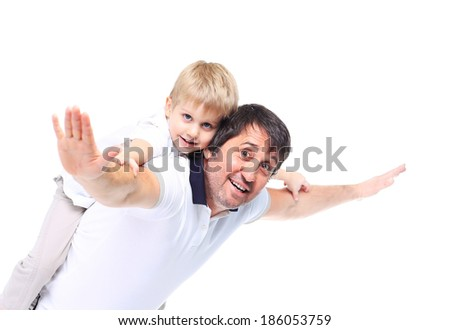 Confident father giving his son piggyback ride against a white background - stock photo