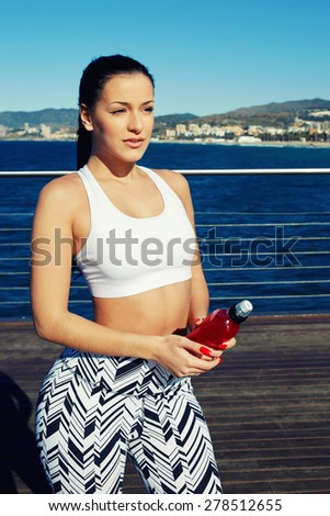 Confident female brunette taking a water break during her daily exercise routine on the beach, attractive fit woman with beautiful figure standing on wooden sea pier  or jetty while having rest,filter - stock photo